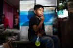 Luego de ir por un jugo a la tienda, Eman se fuma un cigarro fuera del establecimiento. / Foto: Michelle Siu- TIME