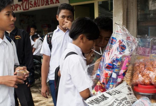 Varios niños compran cigarros en puestos callejeros fuera de la escuela. / Foto: Michelle Siu- TIME