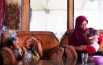Dihan Muhamad fuma frente a su madre mientras ella alimenta a su pequeño hermano en su casa de Garut. / Foto: Michelle Siu- TIME